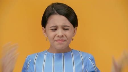elementary age : angry preteen child grimacing and laughing isolated on yellow Stock Footage