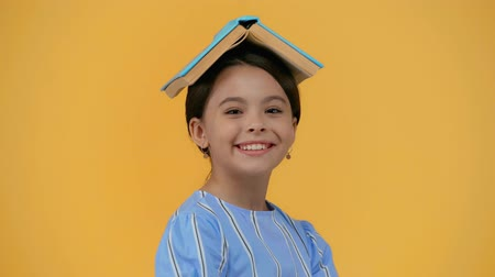 grimacing : excited schoolgirl with book on head grimacing isolated on yellow