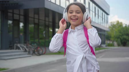 schoolyard : happy schoolgirl listening music in headphones at schoolyard