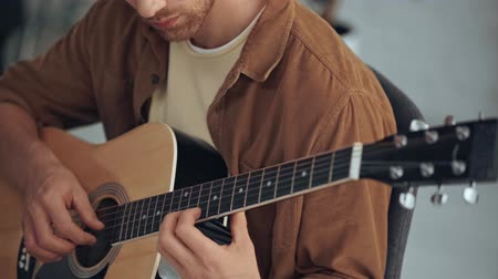 akusztikus : partial view of young man playing acoustic guitar at home