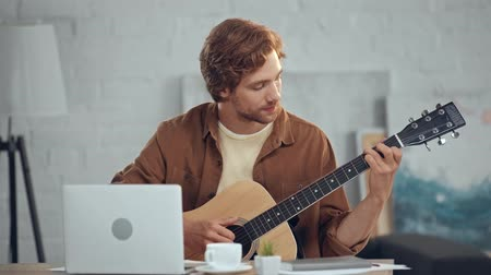 guitarrista : musician playing acoustic guitar during video chat on laptop