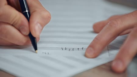 compositor : partial view of musician writing notes on music sheet