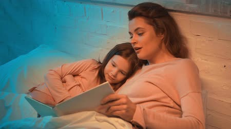 elementary age : mother and daughter lying in bed and reading book together