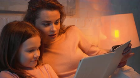 elementary age : mother and daughter reading book together in bed