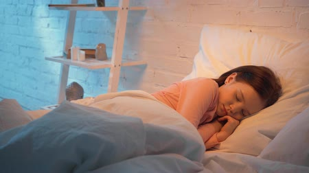 elementary age : mother covering sleeping daughter with blanket at night