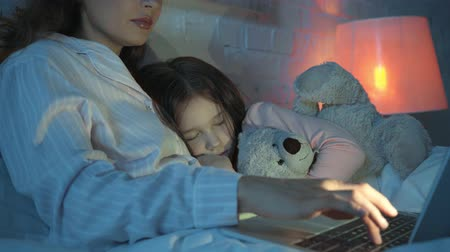 elementary age : mother using laptop while daughter sleeping with teddy bear