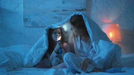 grimacing : mother and daughter grimacing under blanket with flashlight