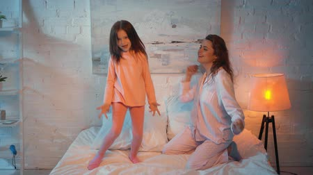 elementary age : mother and daughter dancing in bed at night