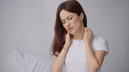 diseased : beautiful woman suffering from neck pain in bedroom