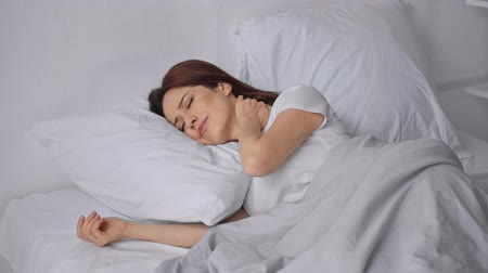 discomfort : woman sleeping in bed and suffering from neck pain Stock Footage