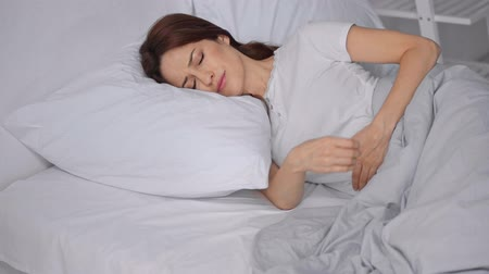bad mood : woman lying in bed and suffering from abdominal pain