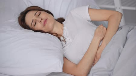 bad mood : woman lying in bed and suffering from stomach ache