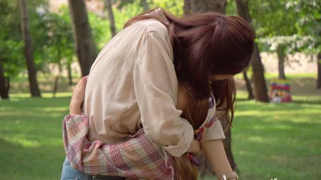 préadolescent : daughter gifting mother bouquet and embracing in park Vidéos Libres De Droits
