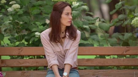 emotive : worried woman waiting someone on bench in park