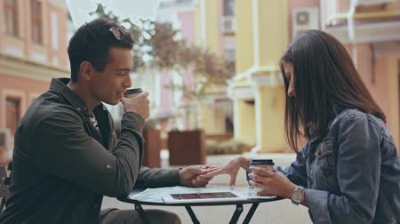 eldobható : interracial couple sitting, holding hands and drinking coffee