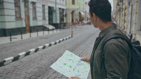 топография : bi-racial man walking with map along street