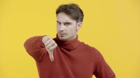 stricken : displeased man in sweater showing thumb down isolated on yellow