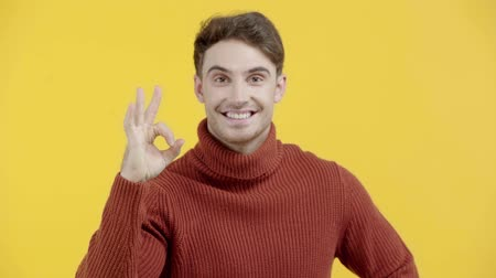 stricken : happy man in sweater showing ok sign isolated on yellow