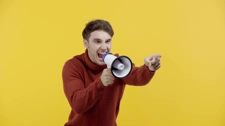 мегафон : slow motion of man in sweater screaming in megaphone isolated on yellow