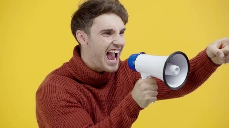 megafono : slow motion of man screaming in megaphone isolated on yellow