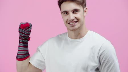 grimacing : funny man talking with sock on hand isolated on pink Stock Footage