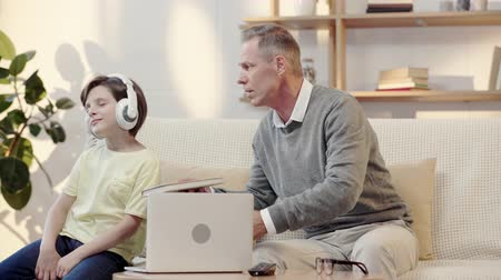 dede : grandfather offering grandson to read book while boy listening music in headphones Stok Video