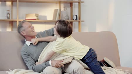 desobediente : grandfather punish naughty grandson with book in living room Vídeos