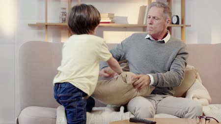 disobedient : naughty grandson hitting granddad with pillow and jumping on sofa