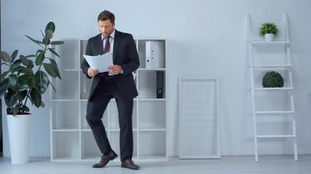 desgaste formal : mature businessman dancing with papers in modern office Vídeos