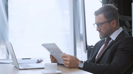 impressão digital : mature businessman using laptop and reading newspaper Stock Footage