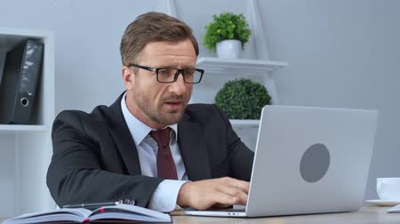 evet : mature businessman in glasses using laptop and showing yeah gesture Stok Video