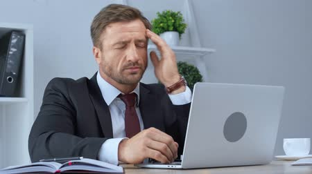use computer : tired mature businessman in glasses using laptop and having headache