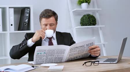 impressão digital : mature businessman reading economic newspaper and drinking coffee in office