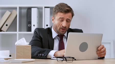 diseased : sick mature businessman using laptop and sneezing in office