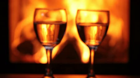 hot wine : Wine glasses in front of fireplace - hands clinking, closeup, rack focus Stock Footage