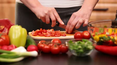 bıçak : Woman hands slicing cherry tomatos for a vegetables salad - side view  of the cutting board at the kitchen table, camera zooming in Stok Video