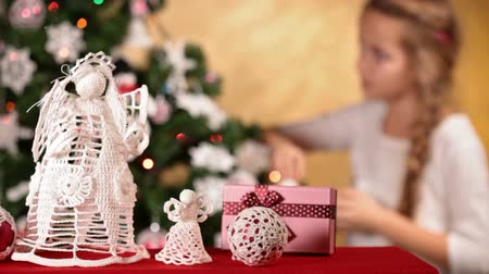 refocus : Girl decorating christmas tree - slowly refocusing to foreground decorations