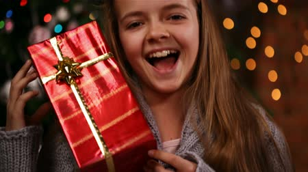 wrapped up : Young girl hands grabbing a christmas present lifting it to her face, laughing with joy - closeup, camera tilting up
