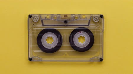 retro revival : Retro music compact cassette reeling tape as if playing, on yellow background - stop motion animation