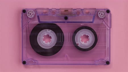 retro revival : Retro music compact cassette reeling tape as if playing, on pink background - stop motion animation