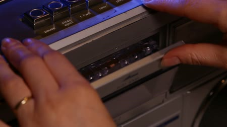 kaseta : Woman hands place a compact music cassette tape in old retro player - closeup, camera tilt up