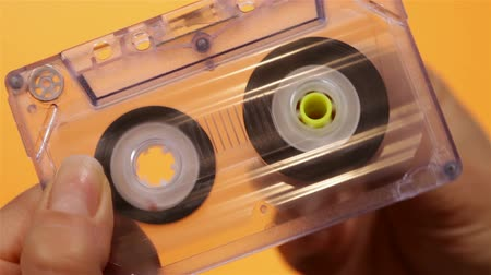 kompakt : Hand holding and reeling transparent compact audio cassette tape - on orange background, closeup Stok Video