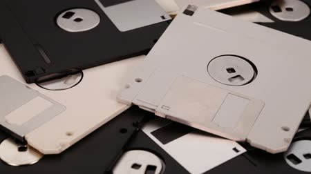 removable : Many 3.5 inch computer floppy disks scattered on a flat surface - vintage technology, closeup, slide above