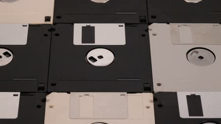 removable : Many 3.5 inch computer floppy disks neatly arranged on a flat surface - vintage technology, closeup, slide above Stock Footage