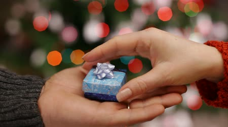 wrapped up : Male hand giving christmas present to female hand - closeup, static camera, blurry xmas lights in background