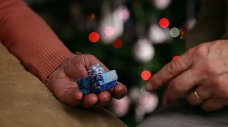 all ages : Senior hands of woman and man giving and receiving small present in front of christmas lights - after all the years together