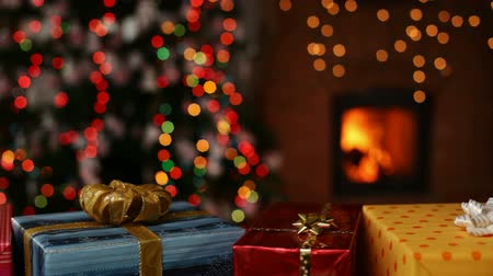 quiet evening : Many christmas gifts in front of fireplace and blurry lights on xmas tree in the evening - camera sliding Stock Footage