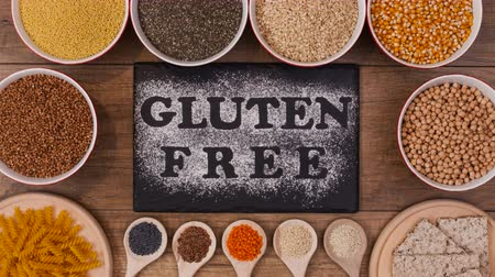 hassaslık : Gluten free diet options presented - various seeds, grains and products slide into frame around black plate with writing in flour, stop motion animation Stok Video