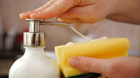 mosogató : Woman hands apply washing up liquid from dispenser on sponge, preparing to wash the dishes at the kitchen sink - close-up, camera slide, slow motion