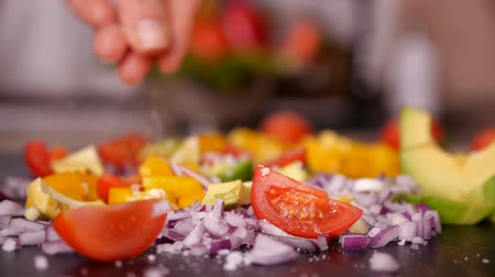 塩漬けの : Woman hand adding salt to vegetables mix prepared on the cutting board - closeup, slow motion